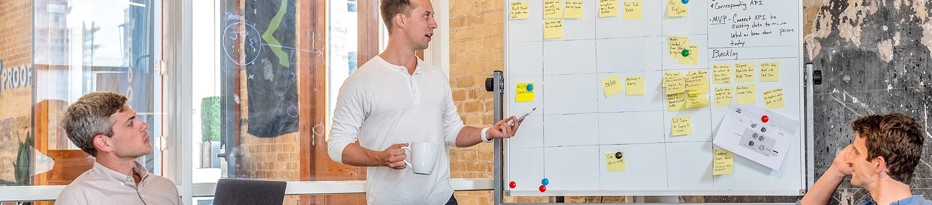 A team sat around a whiteboard of post it notes