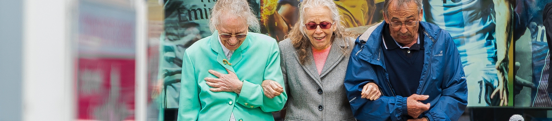 Three elderly friends walking arm in arm