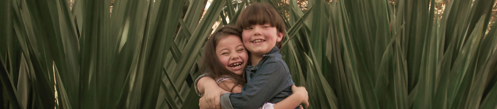 Two children hugging and laughing in front of foliage
