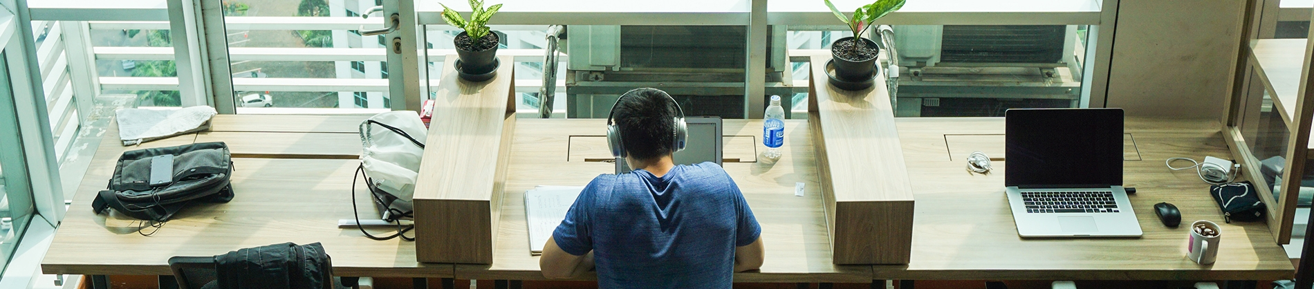 A man sat at a wooden desk with headphones on working