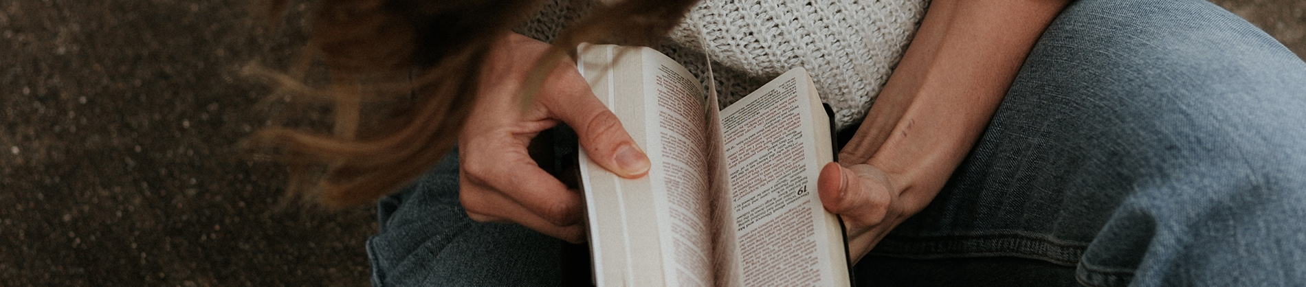 A women sat on the ground looking through her bible