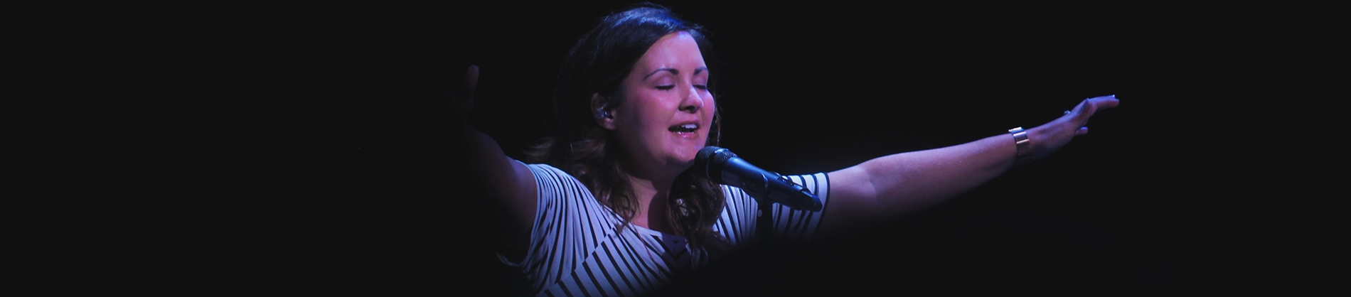 A woman leading worship with a spotlight on her