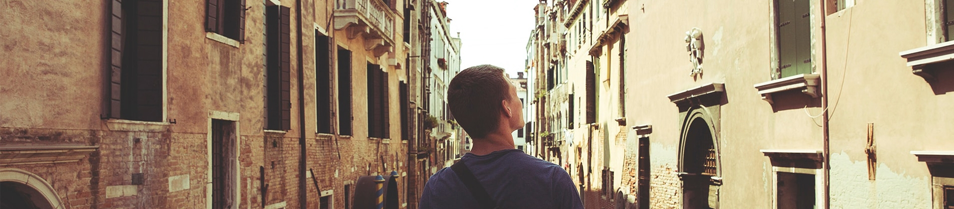 A man stood looking down a row of old buildings