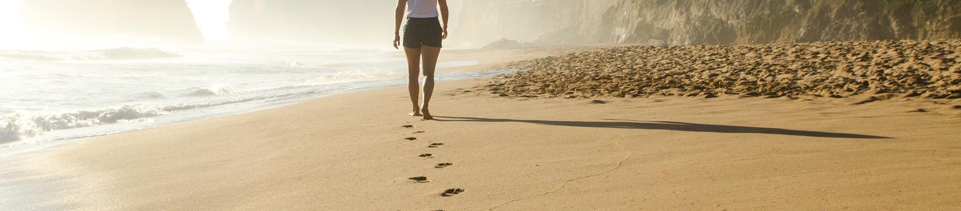 A women walking along the beach leaving footprints in the sand
