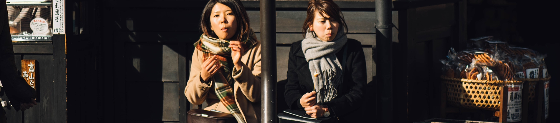 Two women sat on a bench eating