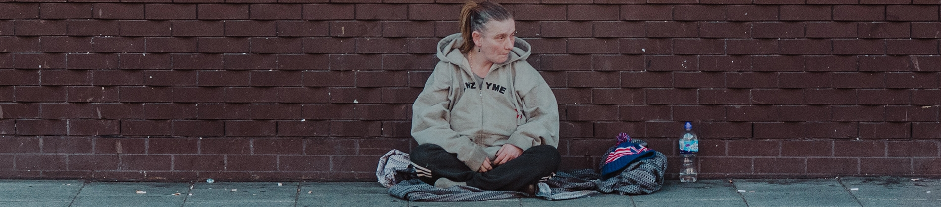 A homeless women sat by a brick wall
