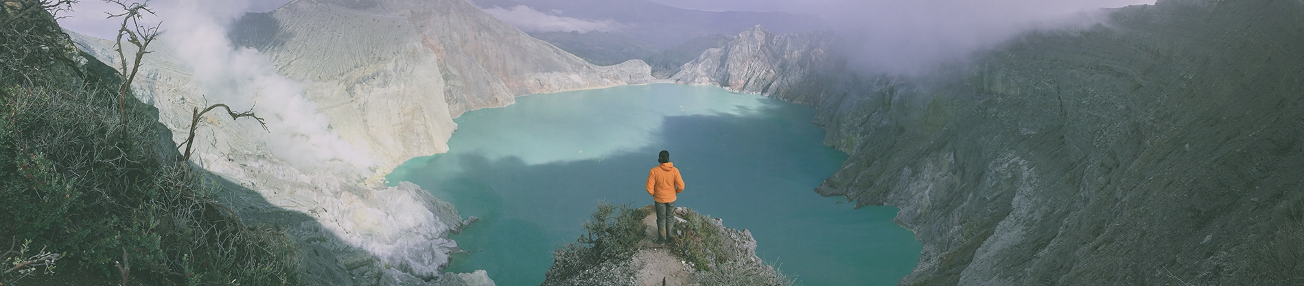 A man looking over a cliff edge into a valley