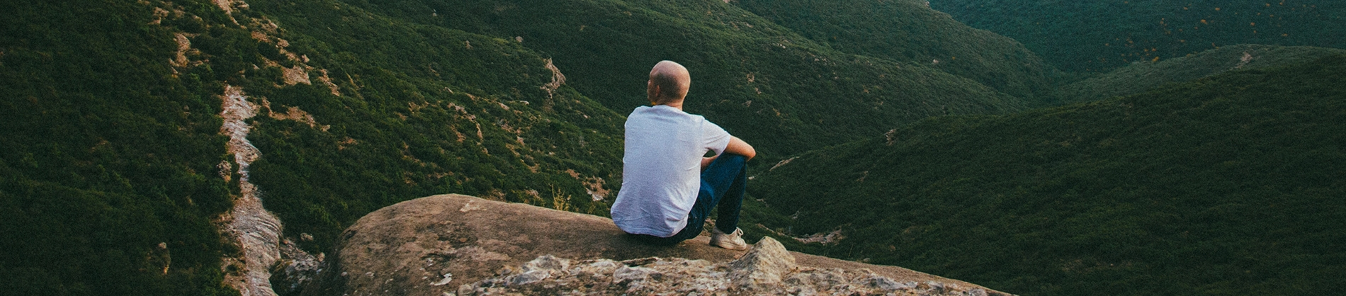 A man sat on the edge of a cliff overlooking a landscape