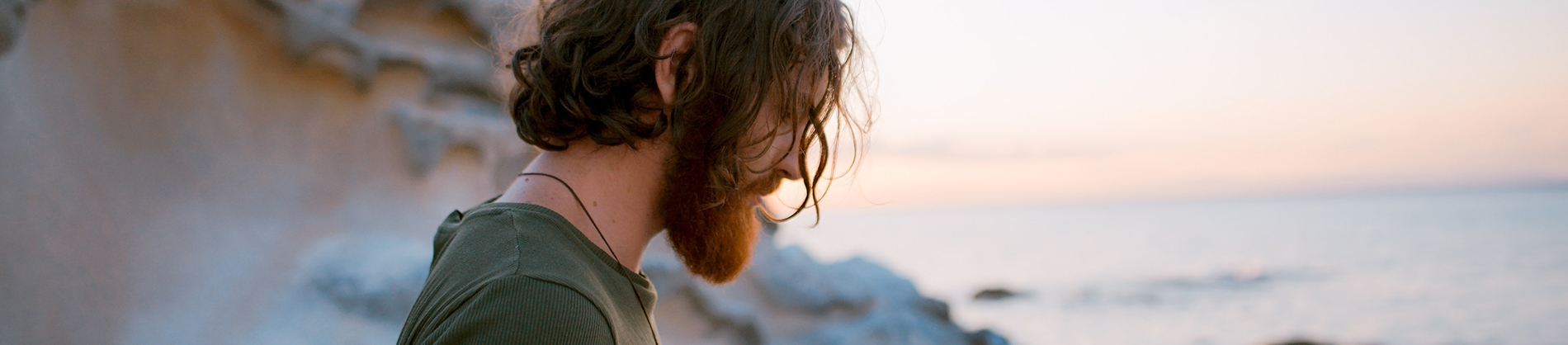 A bearded guy stood by the ocean looking down