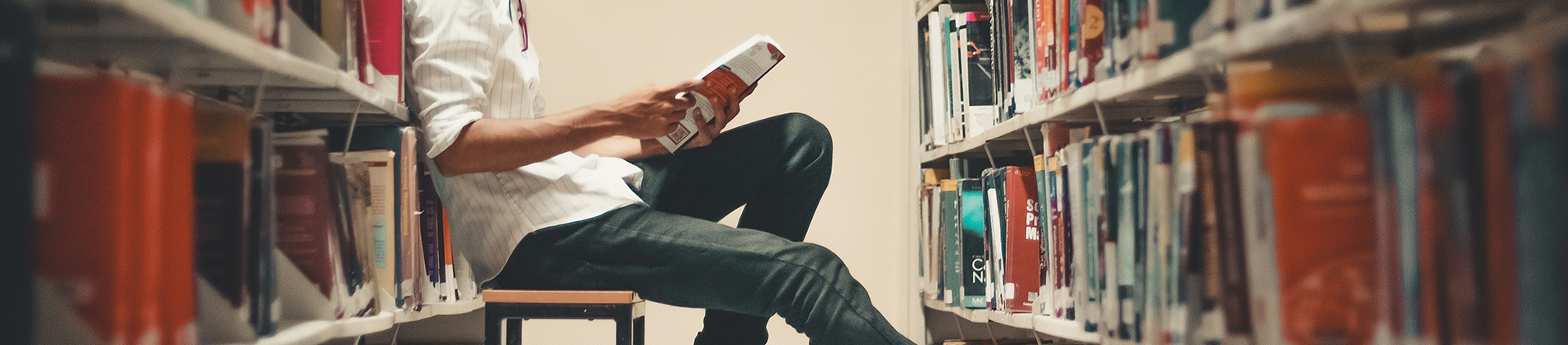 A man sat on a stool leaning on a book case reading