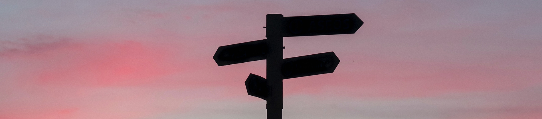 A signpost with a sunset behind