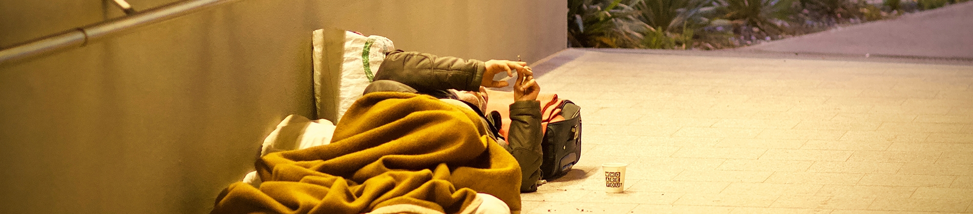A homeless man lying on the floor in a underpass
