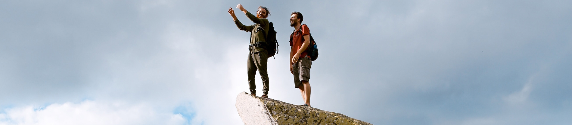 Two guys stood on top of a rock pointing and looking out
