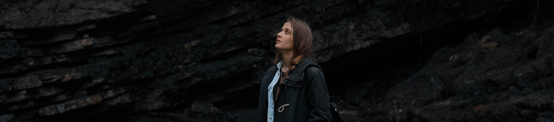 A woman stood in front of a rock face, looking up to the sky