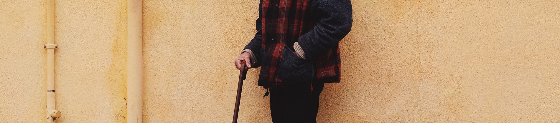 A man stood against a yellow wall with a walking stick