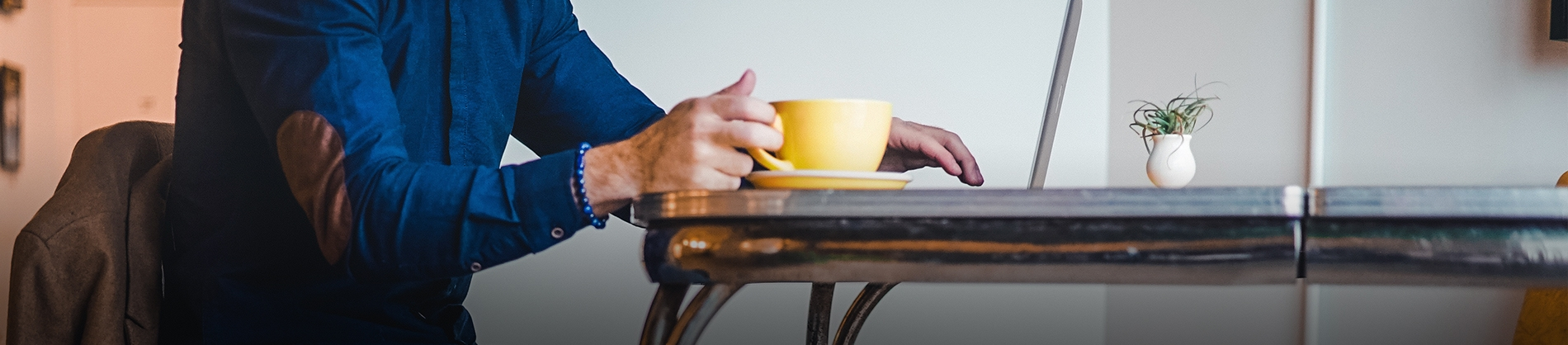 A man sat at a table with his laptop and yellow cup