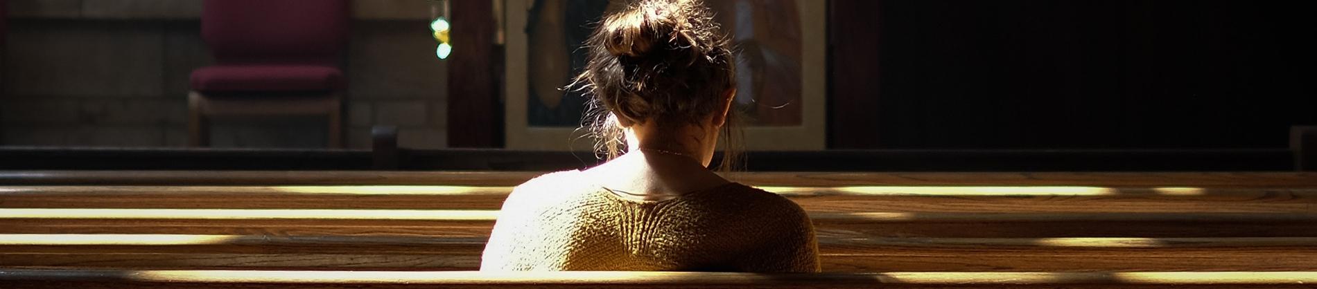 A women sat along in a church pew