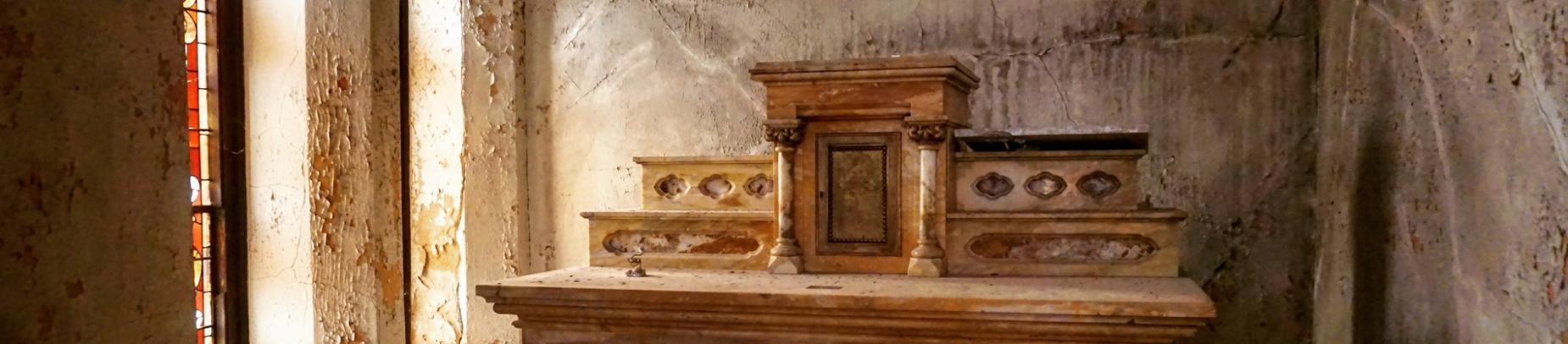 A wooden altar in a run down church room