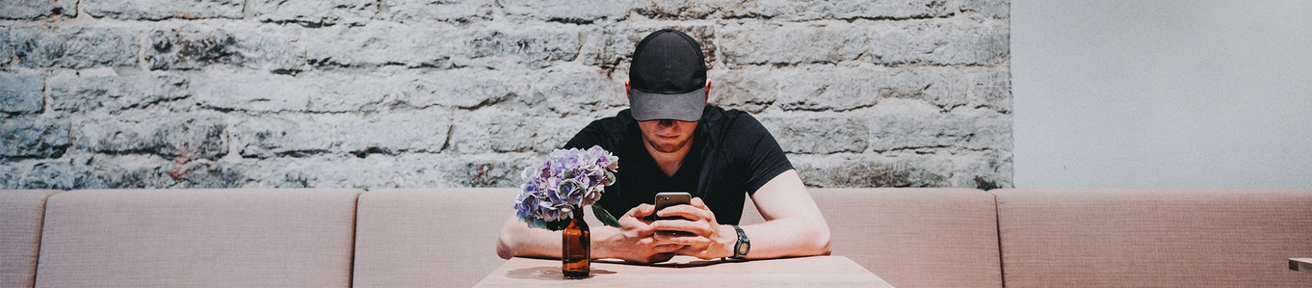 A man sat at a cafe table by himself on his phone