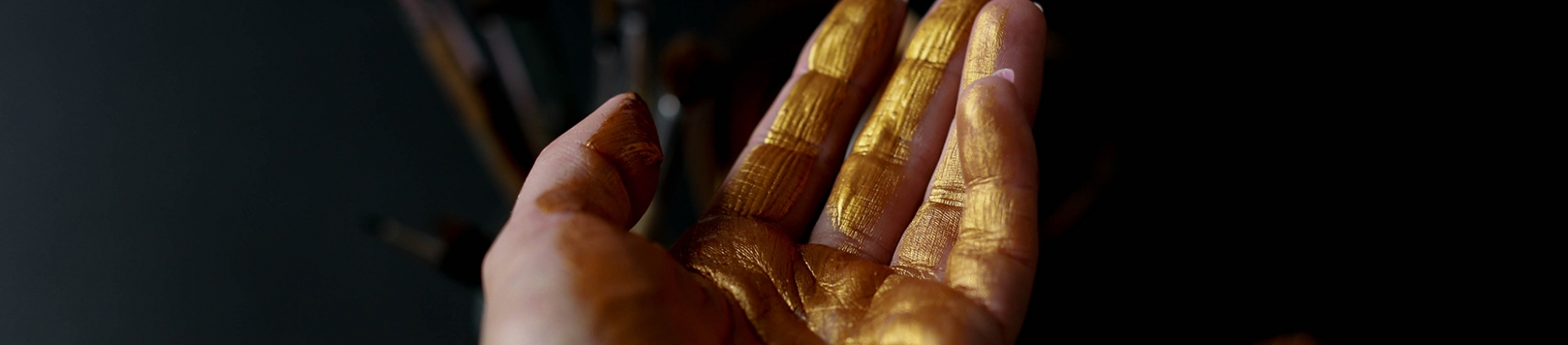 A persons hand with gold paint across the fingers