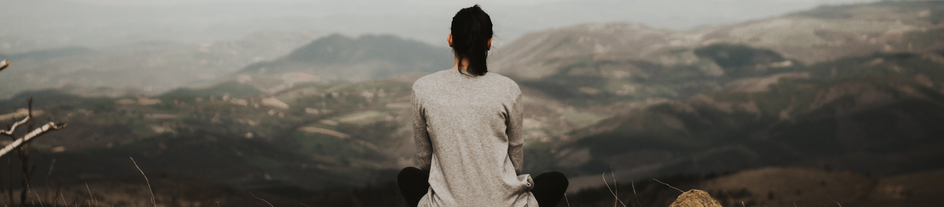 A women sat looking out over a mountain landscape