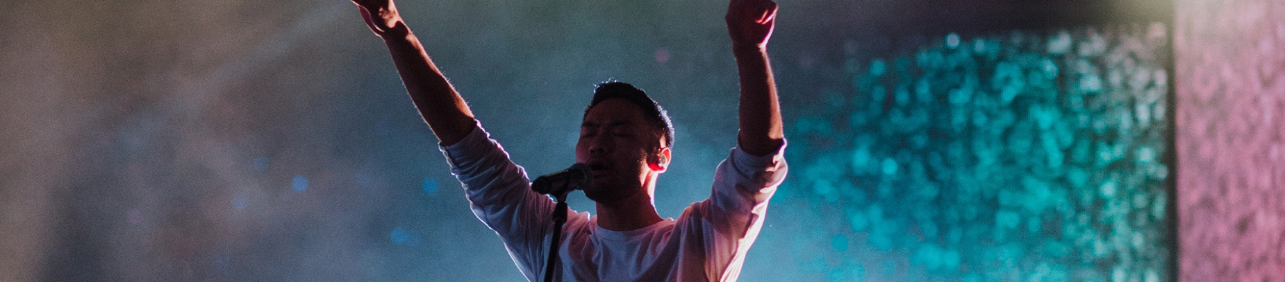 A worship leader singing with hands in the air
