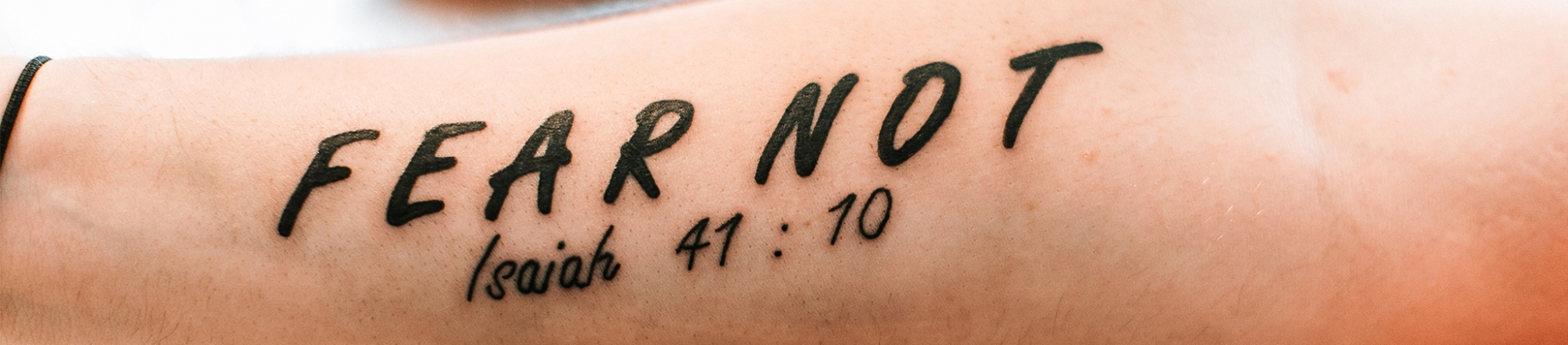 Someones forearm with the words 'Fear not Isaiah 41:10' written on