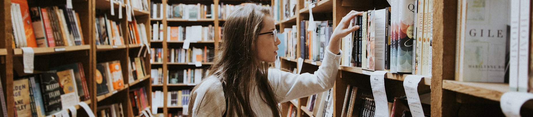 A woman in a library looking through a book shelf