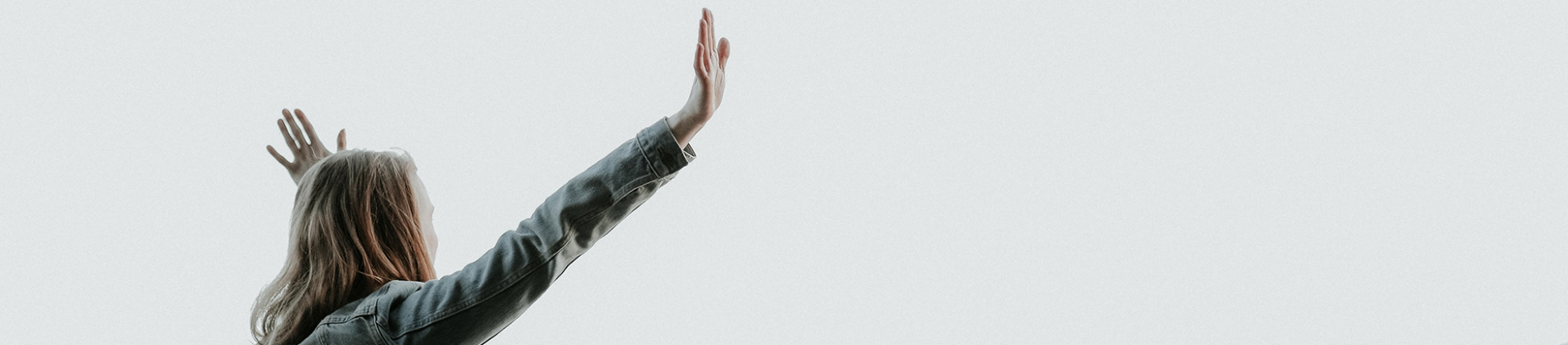 A women in a denim jacket with her arms up in the air