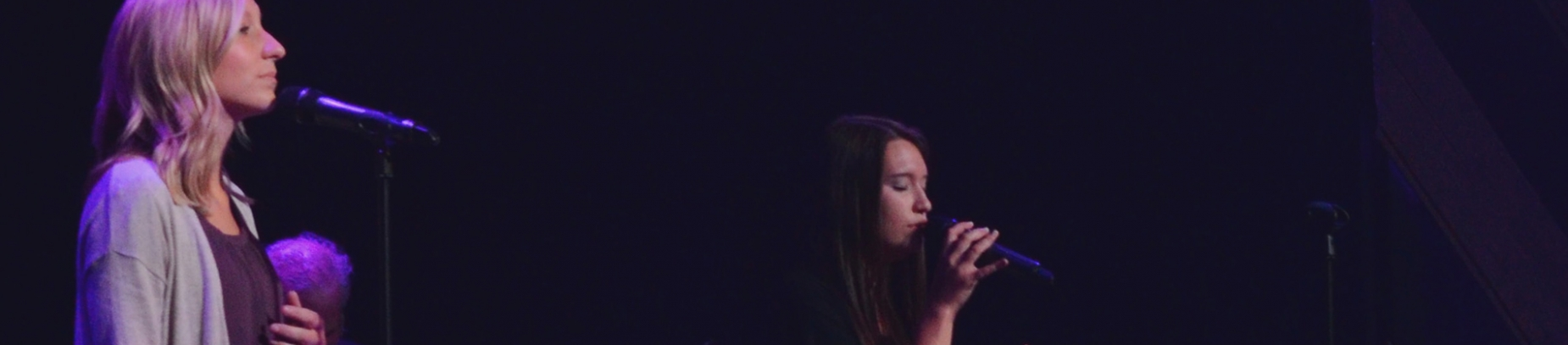 Two women leading worship on a dark stage