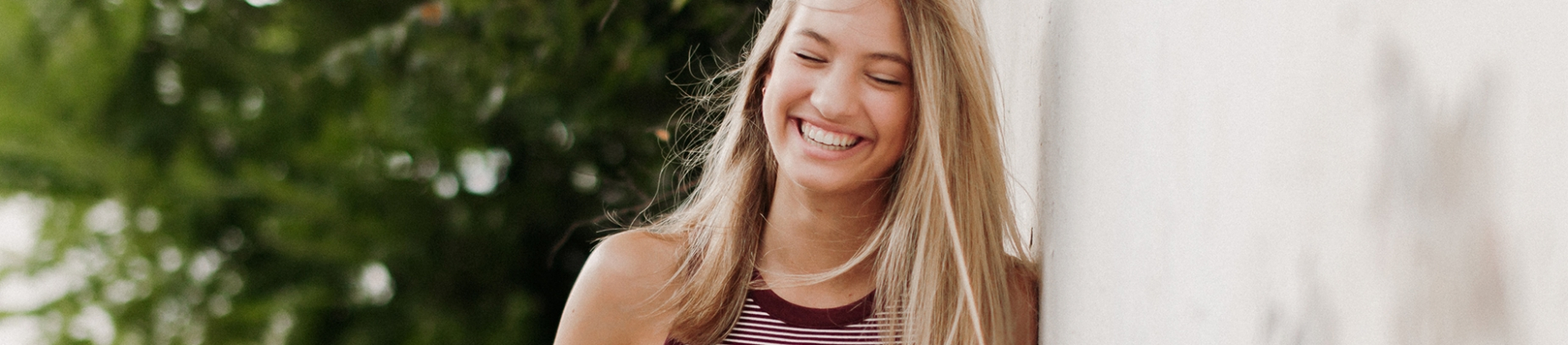 A girl smiling and leaning against a white wall