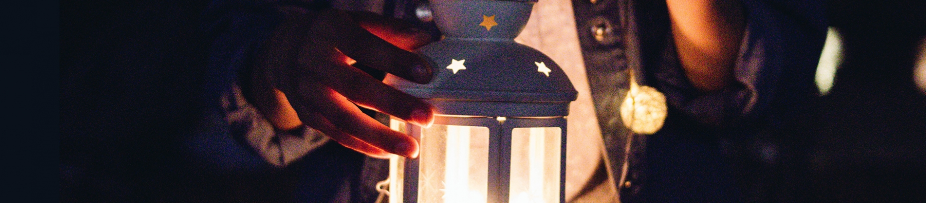 A women holding a lit lantern with stars on it