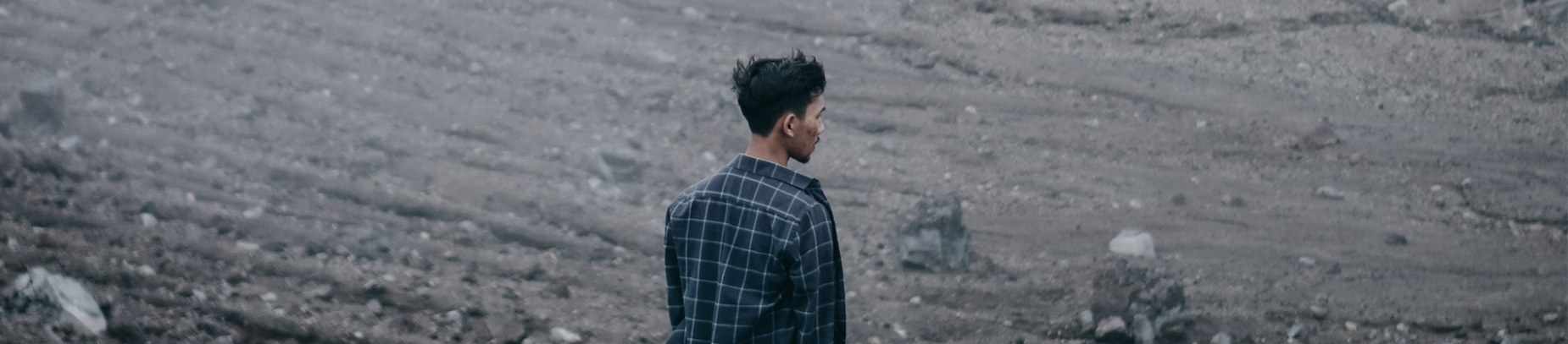 A guy stood in a rocky wasteland