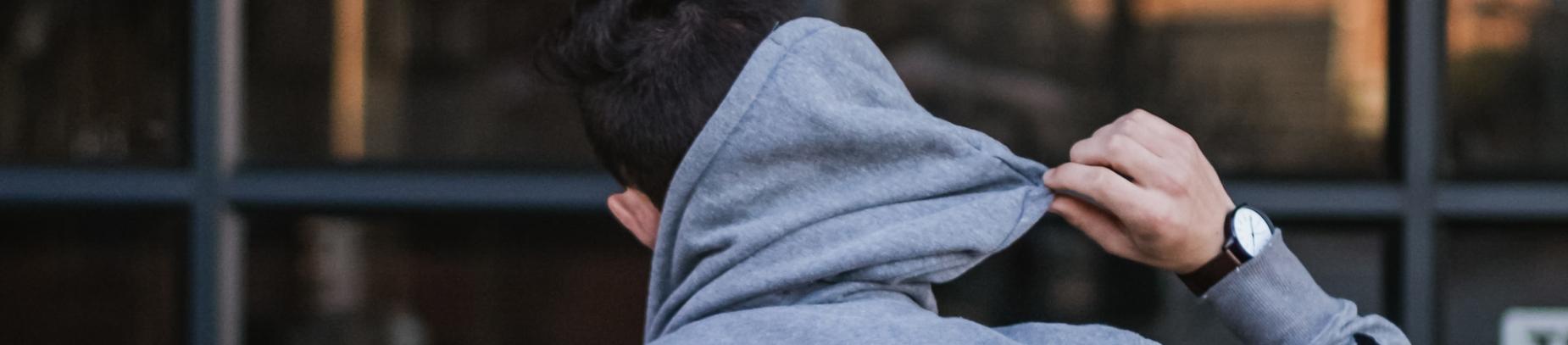 A guy pulling down his hoodie hood off his head