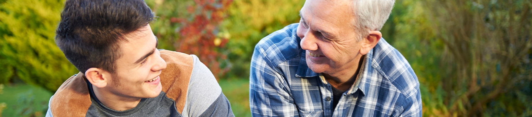 A father and son sat in the garden, smiling at each other