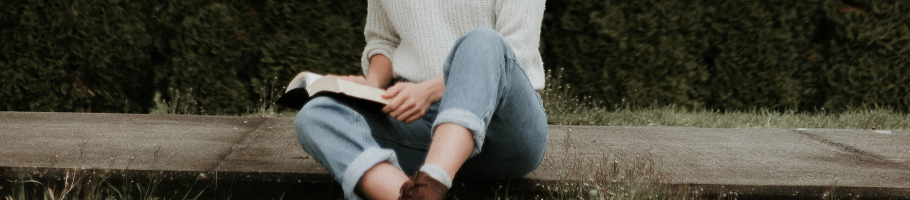 A women sat on the pavement reading the bible