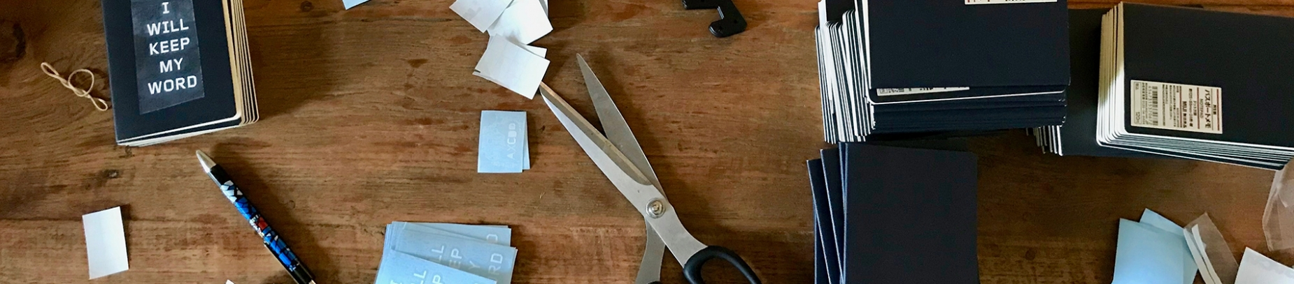 A desk covered in notebooks, scissors and cut up paper