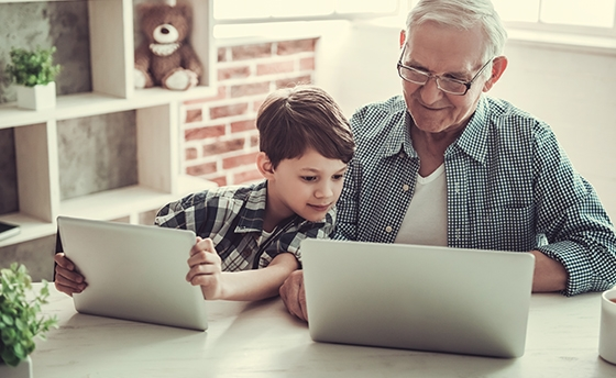 Grandad and Grandson on laptops